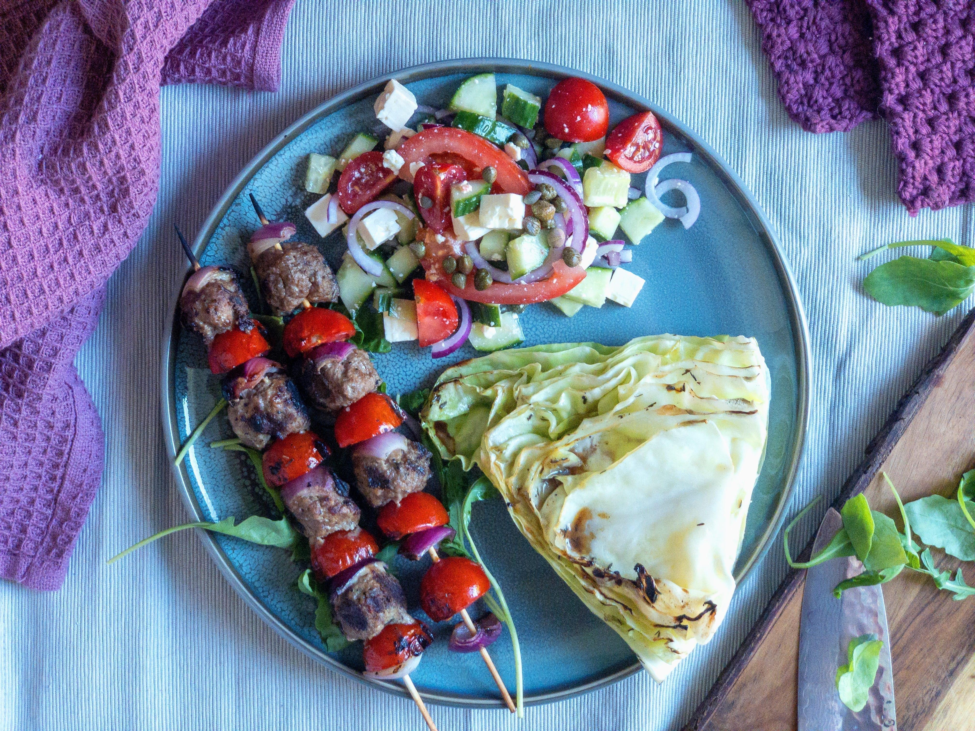 Kødspyd af kødboller, bagt spidskål og en lækker tomatsalat