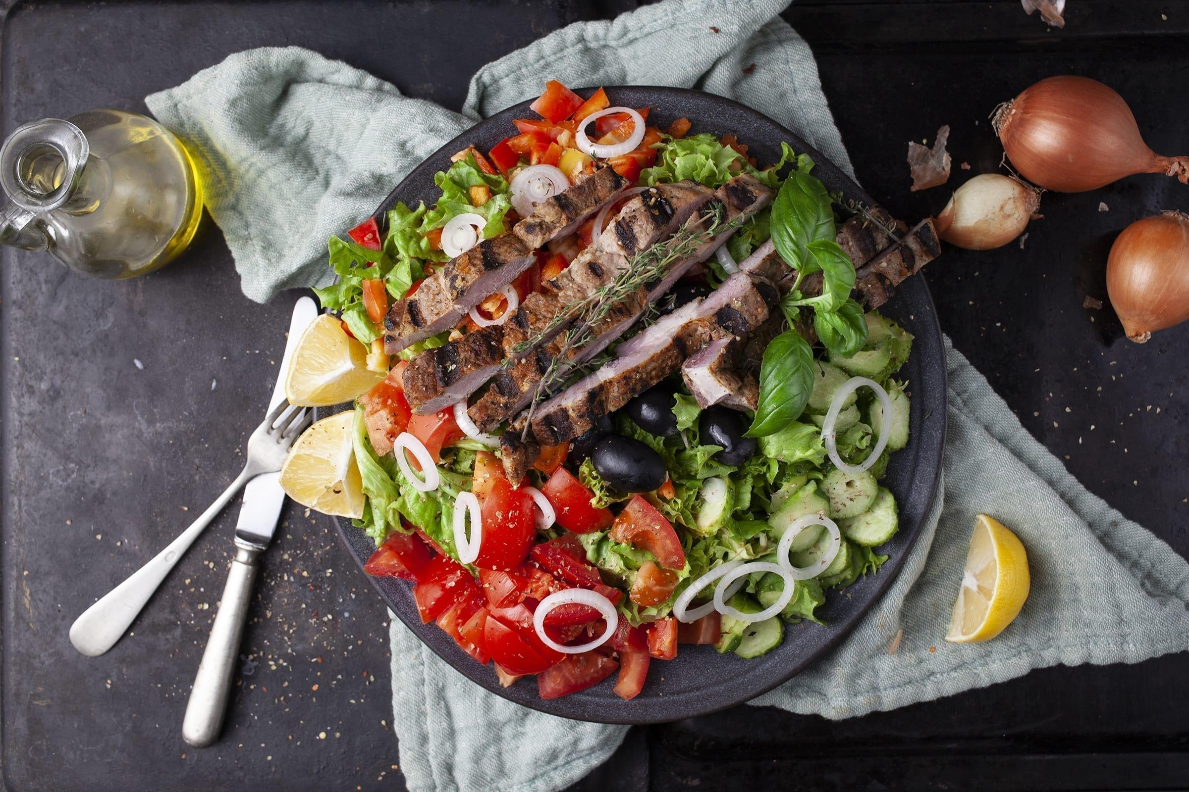 Grillet svinekoteletter på middelhavsinspireret salatbund