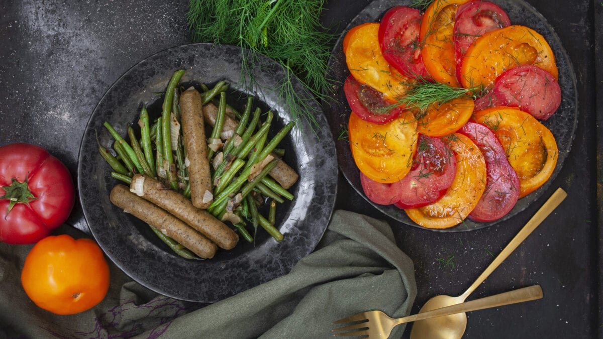Sommerlig ret med oksepølser, bønner og frisk tomatsalat